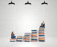 Två unga kvinnor som sitter böcker som tänker om framtid som drömmer royaltyfri foto