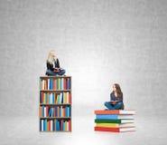 Två unga kvinnor som sitter böcker som tänker om framtid som drömmer Royaltyfri Bild