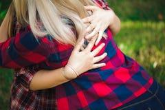Två unga kvinnor som sitter på att krama för gräs arkivbilder