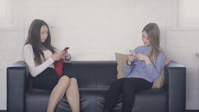 Två unga kvinnor som sitter på soffan inom kontors- och innehavtelefoner stock video