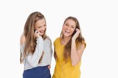 Två unga kvinnor som skrattar på telefonen Arkivfoto