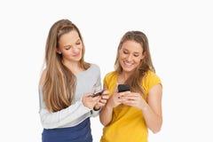 Två unga kvinnor som smsar på deras mobiltelefoner Royaltyfria Foton