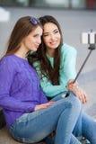 Två unga kvinnor som tar bilder med din smartphone Royaltyfria Foton