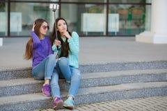 Två unga kvinnor som tar bilder med din smartphone Royaltyfri Foto
