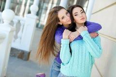 Två unga kvinnor som tar bilder med din smartphone Arkivbilder