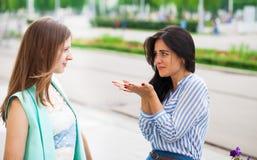 Två unga kvinnor som till varandra talar royaltyfria bilder