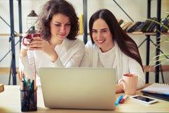 Två unga kvinnor som tillsammans ser bärbara datorn Arkivbild