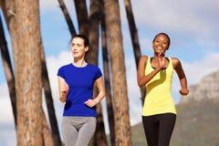 Två unga kvinnor som tillsammans utomhus joggar Royaltyfri Fotografi