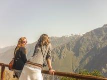 Två unga kvinnor som tycker om sikten av berg Arkivbild