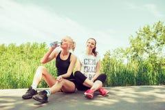 Två unga kvinnor som utomhus placerar i en parkera på solig sommardag Fotografering för Bildbyråer