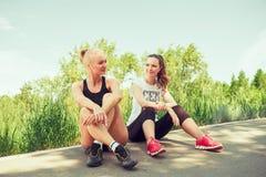 Två unga kvinnor som utomhus placerar i en parkera på solig sommardag Arkivfoto