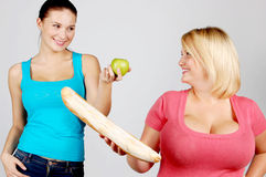 Två unga kvinnor som väljer mat för, bantar arkivbild