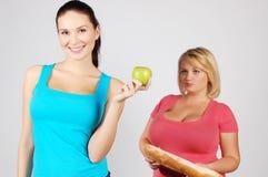 Två unga kvinnor som väljer mat för, bantar arkivbilder