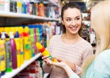 Två unga kvinnor som väljer styiling mousse för hår Arkivfoton