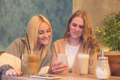 Två unga le flickor som använder mobiltelefonen i kafé- och drinkcof Arkivfoton