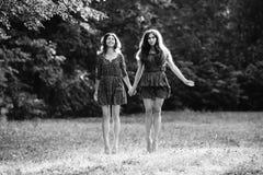 Två unga le kvinnor får att sväva Arkivfoton