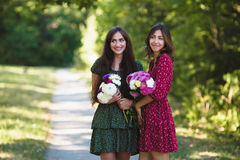 Två unga le kvinnor med blommor Arkivfoto