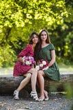 Två unga le kvinnor med blommor Royaltyfri Fotografi