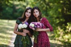 Två unga le kvinnor med blommor Royaltyfria Foton