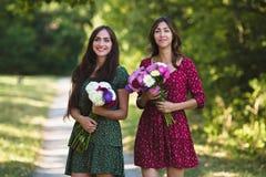 Två unga le kvinnor med blommor Arkivbild