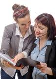 Två unga le kvinnor som arbetar samman med anteckningsboken Arkivbilder