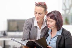 Två unga le kvinnor som arbetar samman med anteckningsboken Fotografering för Bildbyråer