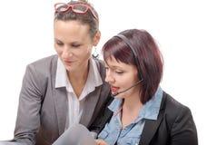 Två unga le kvinnor som arbetar samman med anteckningsboken Royaltyfri Bild