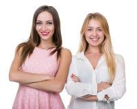 Två unga le kvinnor som isoleras över en vit Arkivbilder