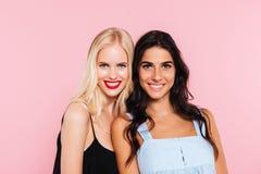 Två unga le kvinnor som poserar i studio Royaltyfri Foto