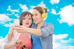 Två unga le kvinnor som tar en selfie Arkivfoto