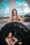 Två unga le lyckliga konditionkvinnor som vilar på ett däck Royaltyfria Bilder
