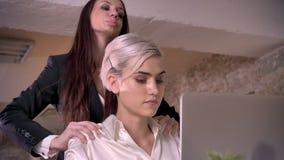 Två unga lesbiska kvinnor i regeringsställning, härlig affärskvinna som masserar annat kvinna och flörta stock video
