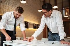 Två unga lyckliga affärsmän som arbetar på ett affärsplan arkivfoto
