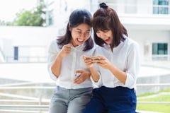 Två unga lyckliga asiatiska kvinnor som har gyckel som spelar socialt massmedia, spelar royaltyfria foton