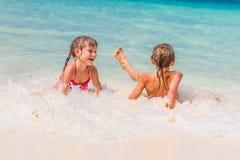Två unga lyckliga barn - flickan och pojken - ha gyckel i vatten, t Arkivfoton