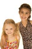 Två unga lyckliga flickor som bär baddräkter som står och ler Arkivfoto