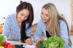Två unga lyckliga kvinnor gör online-shopping vid den minnestavladatoren och kreditkorten Vänner ska laga mat i th Arkivbild
