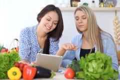 Två unga lyckliga kvinnor som gör online-shopping för framställning av menyn vid minnestavladatoren Vänner som lagar mat i köket Arkivbild