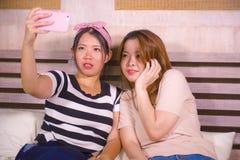 Två unga lyckliga och nätta asiatiska koreanska flickvänner som sitter det hemmastadda sovrummet som tar selfieståendefotoet med  royaltyfria bilder