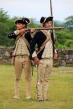 Två unga män klädde som beträffande soldater - att anta muskötdemonstrationen, fortet Ticonderoga, New York, 2014 Arkivbilder