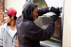 Två unga män som bryter in i hus royaltyfria bilder