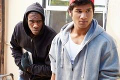 Två unga män som bryter in i hus och stjäler bärbara datorn royaltyfri fotografi