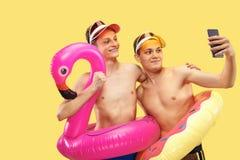 Två unga män som isoleras på gul studiobakgrund royaltyfri fotografi