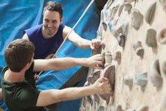 Två unga män som ler på de och klättrar i en inomhus klättringidrottshall fotografering för bildbyråer