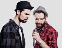 Två unga män som sjunger med mikrofonen bakgrund isolerad white Arkivfoto
