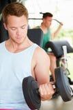 Två unga män som utbildar i idrottshall med vikter Arkivfoton