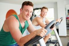 Två unga män som utbildar i idrottshall på att cykla maskiner tillsammans royaltyfria foton