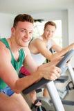 Två unga män som utbildar i idrottshall på att cykla maskiner tillsammans Arkivbild