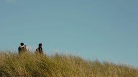 Två unga män står i högväxt gräs, ett av dem som tar bilder på hans telefon stock video