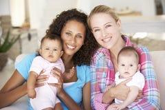 Två unga mödrar på Sofa At Home fotografering för bildbyråer